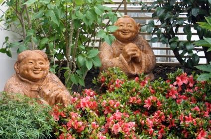 Bouddhas heureux, azalées en fleur, lilas blanc et camélia