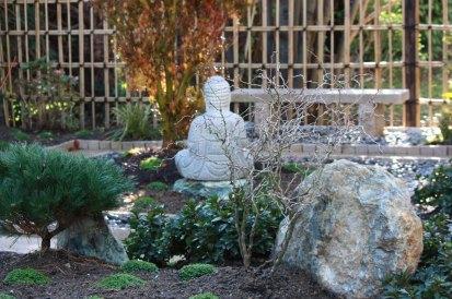 Le bouddha en granit apporte sa présence au jardin. Pour le contempler, un banc du même granit lui fait face, adossé à la clôture japonaise en bambous.