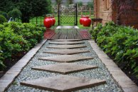 Une allée géométrique traverse le jardin japonais et la terrasse, aboutissant à un portillon en bambous qui s'ouvre sur le jardin arrière.