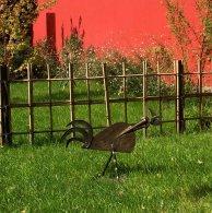 Un jardin plus informel à l'arrière des habitations est éclairé par un mur rouge, sur lequel jouent les ombres des végétaux.