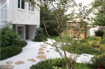 L'accès au pavillon japonais se fait par un pas qui traverse le jardin sec. Au premier plan, un cerisier du Japon à floraison blanche