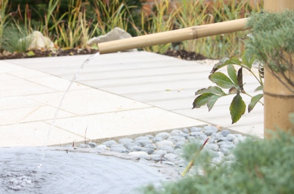 Fontaine japonaise, dallage en granit et bois béton et en arrière plan un jardin de graminées
